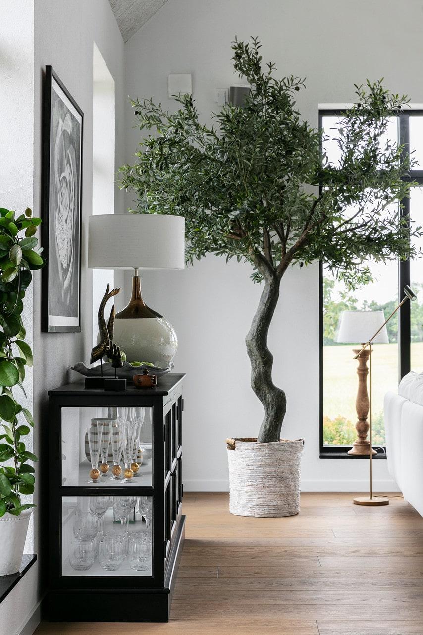 Ett rum med högt i tak kräver stora växter. Det konstgjorda olivträdet hjälper till att sudda ut gränsen mellan ute och inne. Lampa i fönstret, PR Home. Golvlampa, Lamphuset.