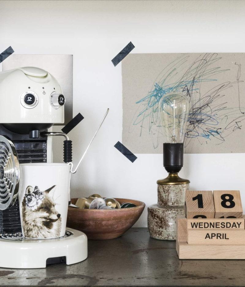 Nespressomaskinen har Angelica fått i födelsedagspresent. Den lilla skålen är ett fynd från uthuset och lampan ett loppisfynd. Kopp från H&M home, kalender från House doctor. Teckningen har Helmi ritat.