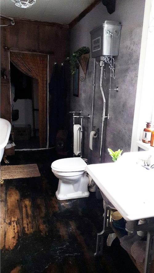 Den gammaldags toaletten har Camilla köpt i England. Golvet i badrummet är nytt klinker som ser ut som trä. För att få det att se gammalt ut har hon hällt ut cement över det.
