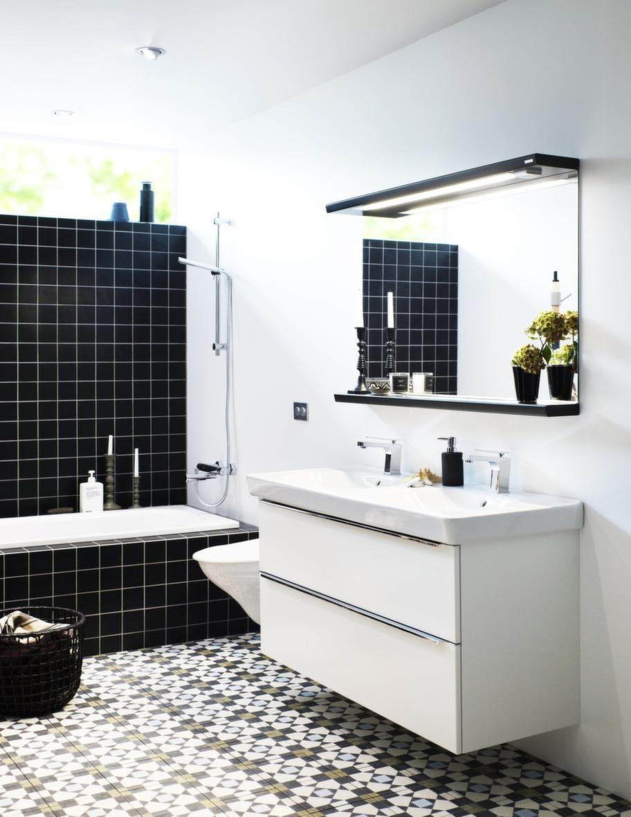 """<span style=""""text-decoration: underline;"""">Tidy, Vedum - Kontraster mellan svart &amp; vitt</span><br>Badrumsserien Tidy har tvättställ med generösa avställningsytor och rena linjer. Kontrasterna mellan svart, vitt och det mönstrade golvet ger miljön karaktär. En nyhet för i år är ett dubbeltvättställ och tvättställ i svart porslin. Levereras monterad.<br>Pris: Tidy tvättställspaket bestående av underskåp i vitt, lådfront Plain vit med grepplist krom och dubbeltvättställ i porslin, 16 195 kronor, spegel med spegelhylla, spegelbelysning och 230 V uttag, 6 123 kronor."""