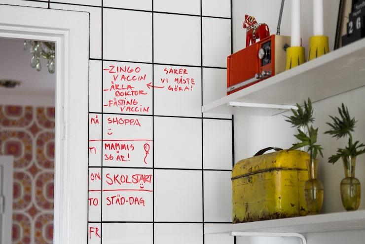 I köket används kakelväggen som familjens kalender. På hyllan står en gammal matlåda köpt från USA på E-bay. Transistorradion har tillhört Cornelias mammas.