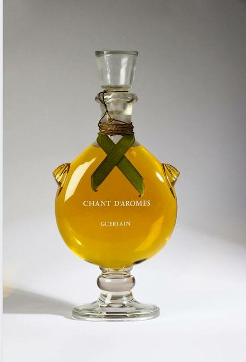 År 1962 lanserade parfymhuset Guerlain sin doft Chant d'Arome i en lyxig flaska med slipad kristallpropp. Det olivgröna sammetsbandet pryder flaskan som tillverkades av Lalique, Frankrike. Guerlain är ett av de äldsta parfymhusen i världen och grundades1828. En oöppnad flaska från 70-talet i gott skick kan i dag kosta ett par tusen kronor på den internationella samlarmarknaden.