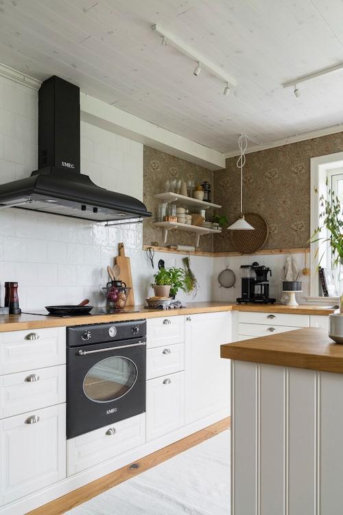 Köket går i klassiskt lantlig stil med fasade luckor och skålhandtag. Kaklet från Gysinge byggnadsvård är ett fasat kakel, tillverkat och glaserat för hand, vilket ger en rustik och genuin känsla. Köksinredning från Ikea, handtag från Smedstorp, spis och fläkt från Smeg.