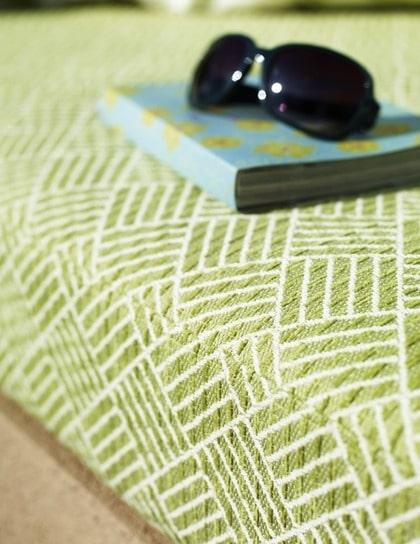 Stoppad dyna. Dynan är klädd med det gröna tatamiinspirerade tyget Tamia i färgen Pistache nr 4650/02 ur kollektionen Nemo, 1 400 kronor/meter från Manuel Canovas/ Cadoro. Bokomslag av papper från block med dekorark, färgstark mix, 73 kronor, Panduro hobby. Solglasögon H&M.