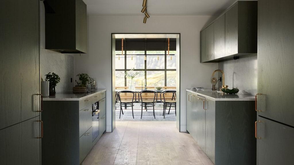 Väggarna i köket är målade i en varmvit kulör som lyfter köksluckornas gröna ton. I bakgrunden syns orangeriet.