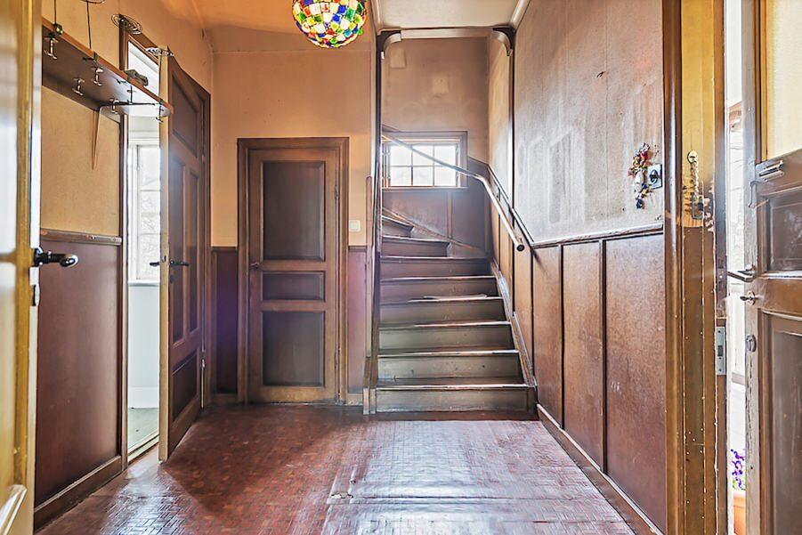 Rymlig och möblerbar hall med fint ljusinsläpp via fönsterparti i trappa. Plastmatta och delvist tapetserade väggar.