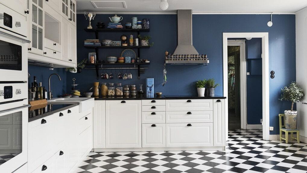 Stilrent kök med vita luckor, bänkskiva i svart natursten samt ett schackmönstrat klinkergolv.