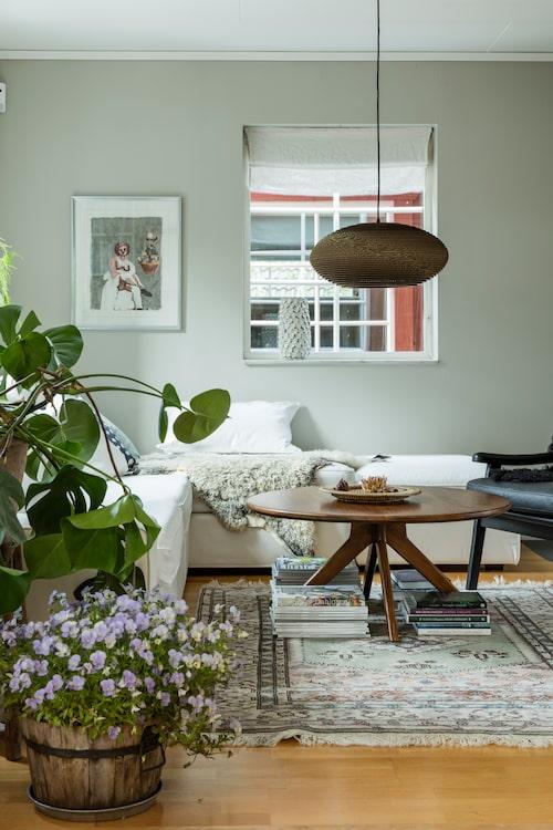 I vardagsrummet finns mycket olika texturer och textilier. Fåtölj, Furninova. Soffbord, Ellos. Taklampan är i ekologisk wellpapp, Graypants. Litografi av Cecilia Sikström.