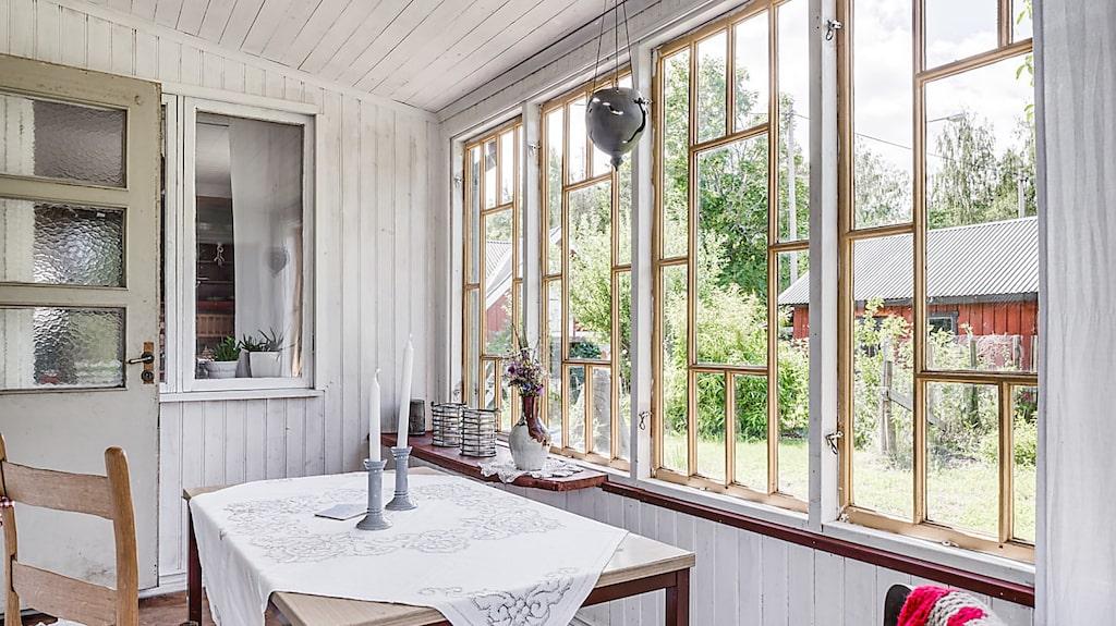Verandan med glasparti samt trägolv och träpanel på väggar och tak.