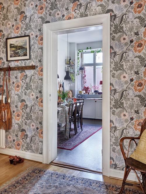 Vy från hallen in i köket som har utsikt ut mot innergården. Tapet Anemone, Midbec.