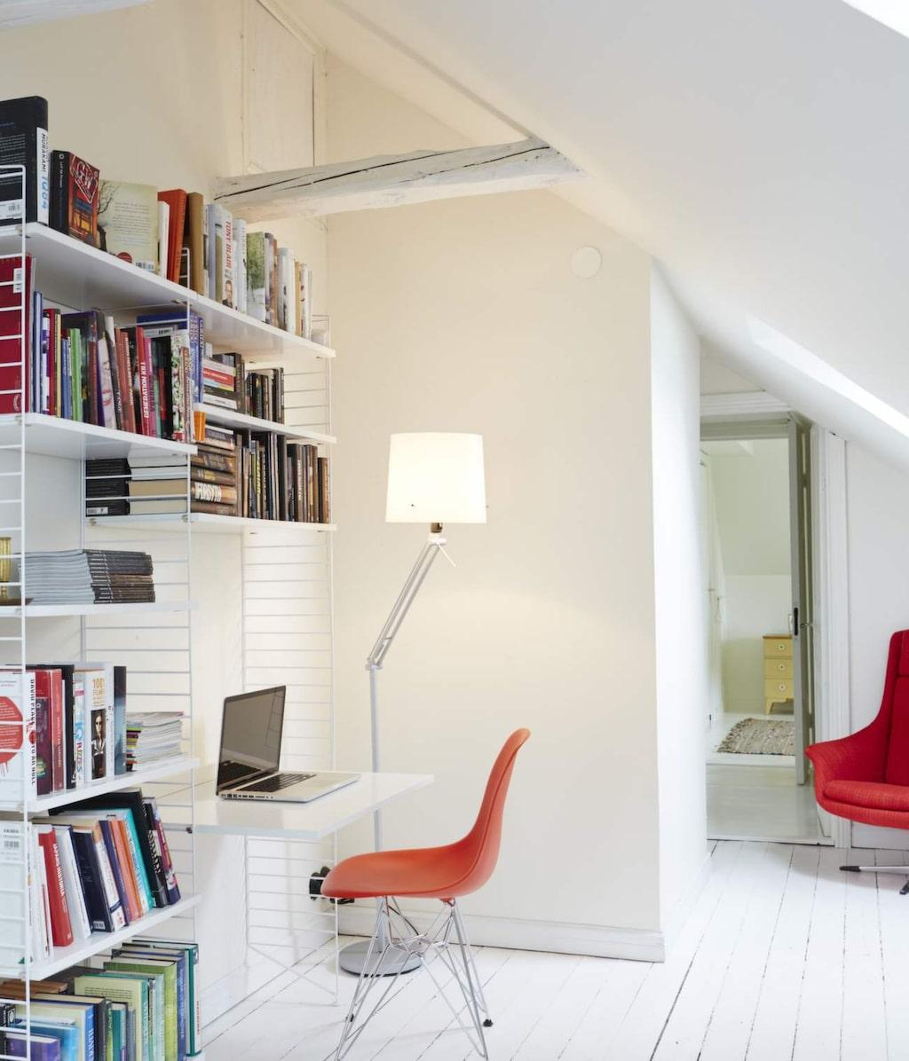 I anslutning till stringhyllan i gästrummet har det gjorts plats för ett litet arbetsbord. Eames-stolen blir en välkommen färgklick.