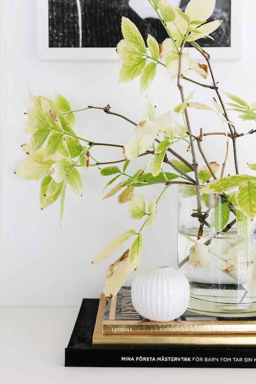 Skirt gröna löv med synligt grenverk i rejäl glasvas utgör ett effektfullt blickfång på sidobordet i hallen. Glasvasen är en gåva. Liten vit vas från Kähler.