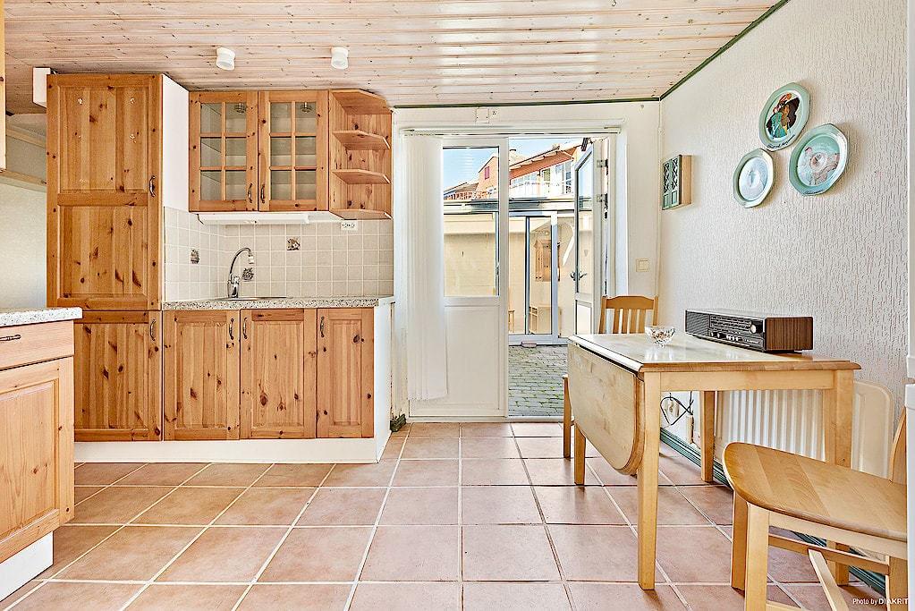 Köket har klinker på golvet, inredning av trä och kyl, frys, spis och fläkt. Här ryms även ett matbord med stolar.