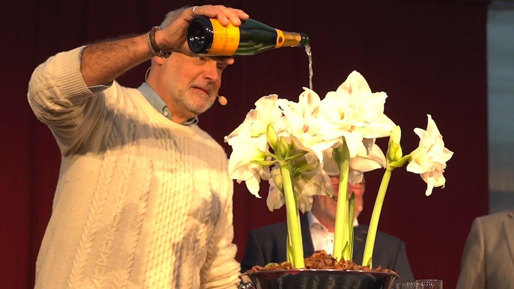 Tv-profilen var inte helt bekväm med att hälla just champagne över blomman. Men visst gick det bra till sist!