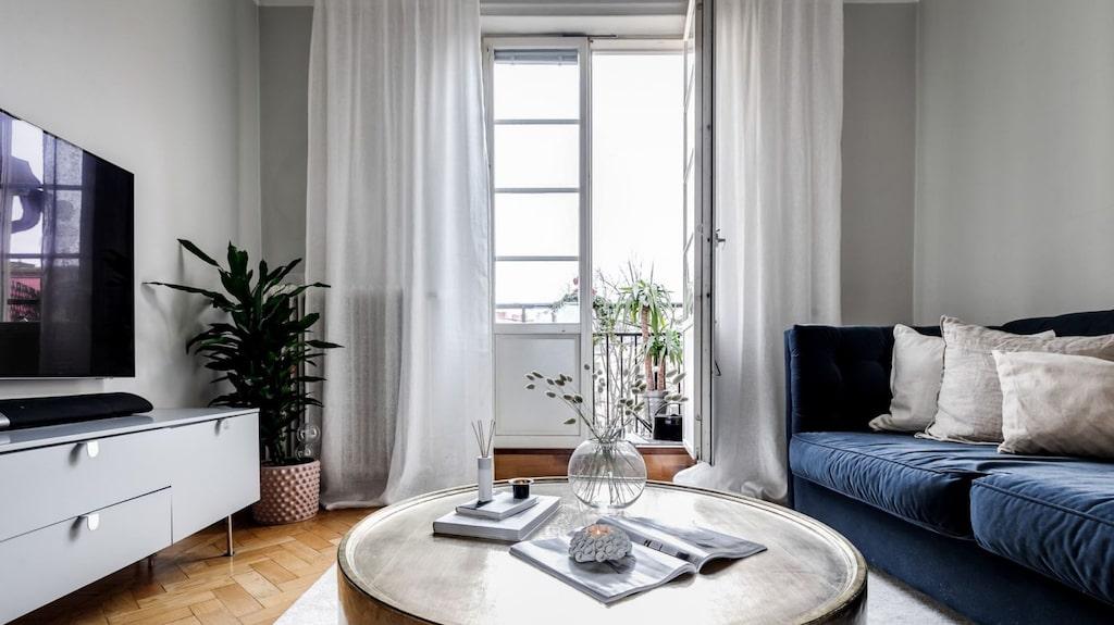 Ljust vardagsrum med fiskbensparkett och gråmålade väggar.