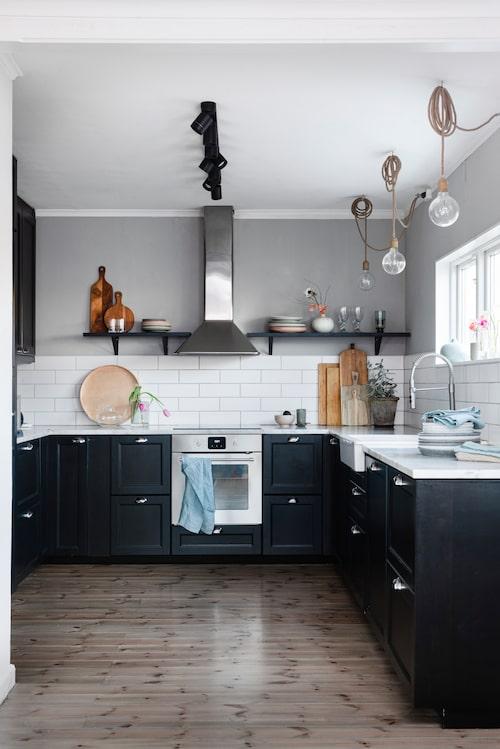 Det svarta köket går i en tidlös stil med bänkskivor av vit carraramarmor. Glödlampor med naturfärgade sladdar, Watt & Veke. Fläkt, spis, ugn, köksblandare och rund träbricka, Ikea.