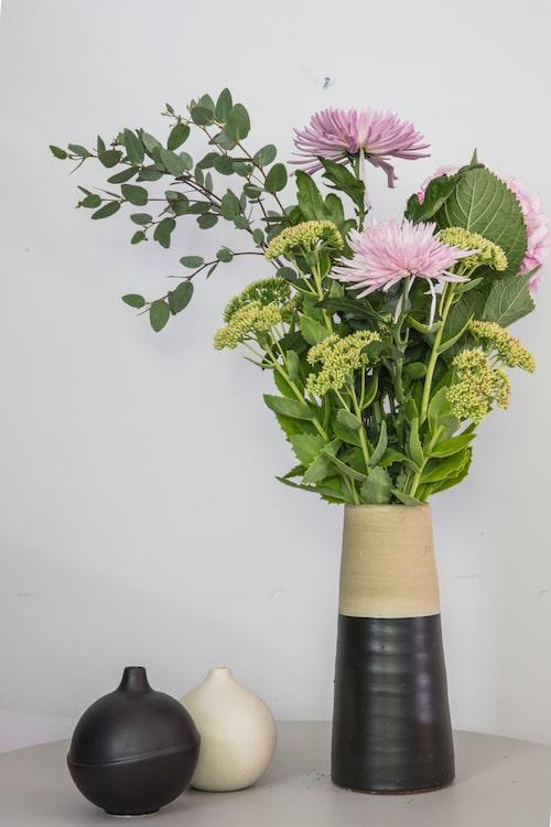 En hög bukett i trendig keramikvas lyser upp vilket rum som helst. Här syns kärleksört tillsammans med rosa krysantemum, rosa hortensia och späd eukalyptus.