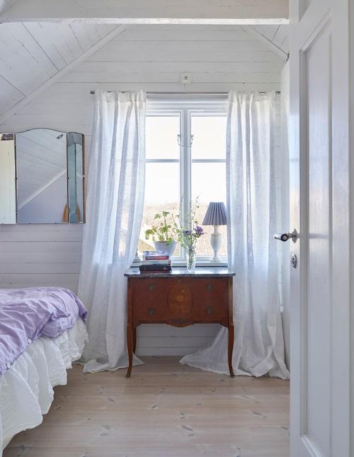 I Julia och Viktors sovrum är taket numera öppet upp till nock för att ge det mera rymd. Den lilla byrån och spegeln är arvegods. Julia har målat om lampskärmen med väggfärg som blev över i sovrummet.