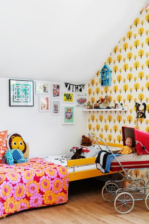 """Barnens rum är delvis tapetserat med en gulmönstrad tapet. Det storblommiga överkastet är ett gammalt innertäcke som Isabelle hittade på sina föräldrars vind. Tapet, Dotty från Ferm Living. """"Dockvagnen hade jag som liten, jag har i min tur ärvt den av min kusin"""", berättar Isabelle."""