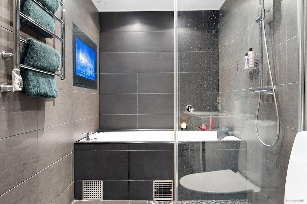 Lyxigt badrum utrustat med jacuzzi bubbelbadkar och inbyggd TV, takdusch/handdusch med glasvägg, wc, handdukstork, kommod med spegel ovan samt tvättmaskin och torktumlare. Golvvärme, spotlights och högtalare i taket.