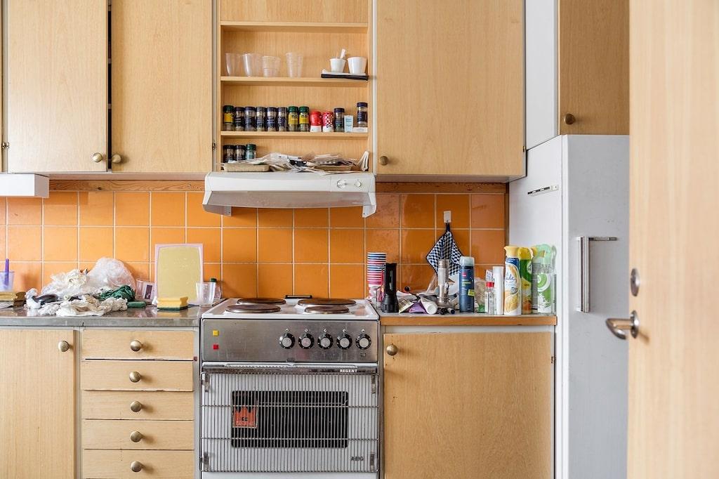 Del av köket. Ljusa skåpluckor och terrakottafärgat kakel ovan arbetsbänk.