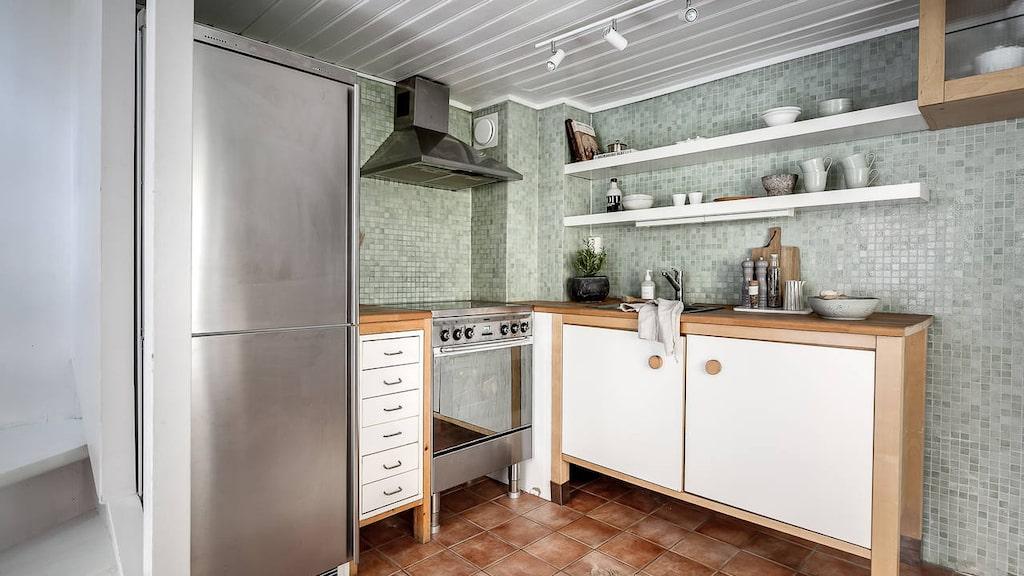 ... och köket med vit inredning, köksbänkar i trä, platsbyggt skåp...