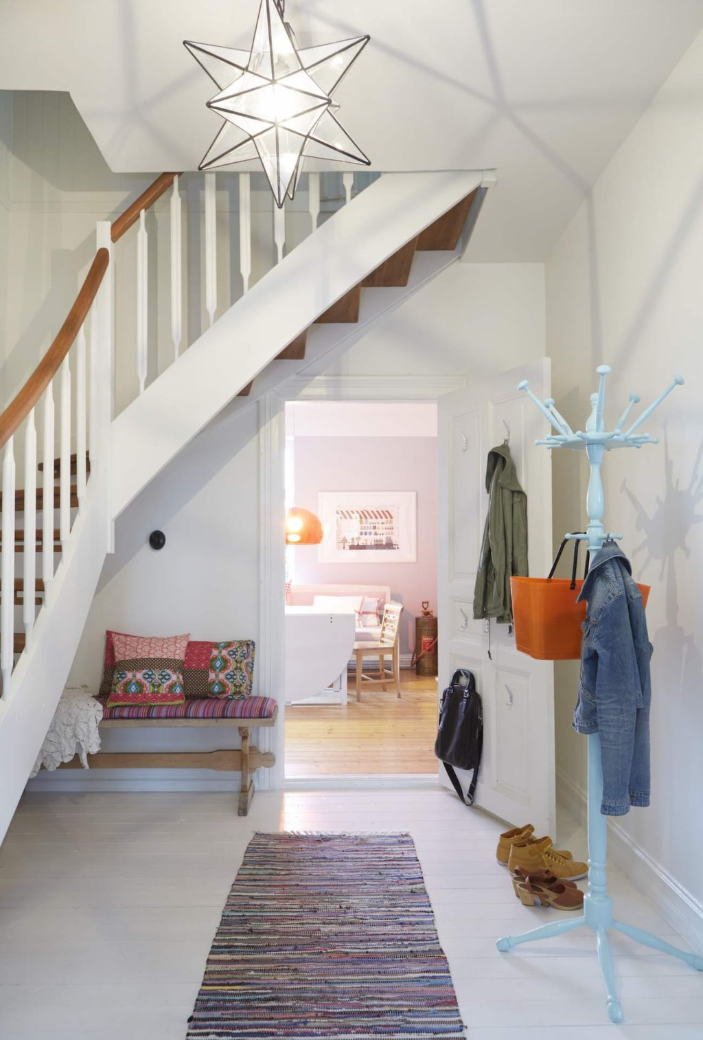 I hallen som förbinder verandan, arbetsrummet, köket och vardagsrummet står klädhängaren som Cecilia målat ljust blå. Den orange plastväskan kommer från Hinza.