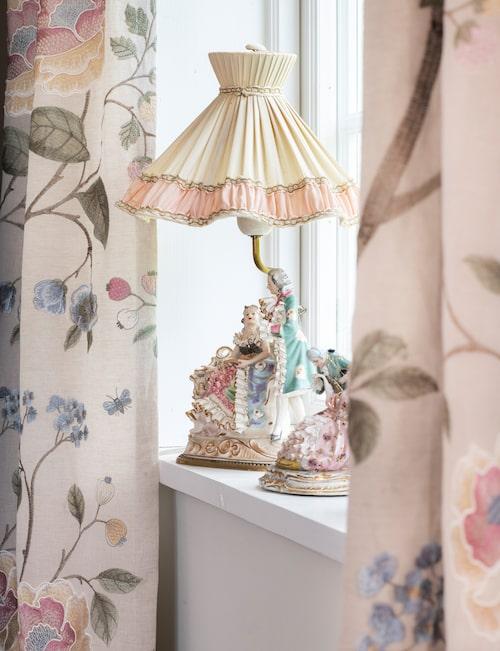 Fönstret ramas in av klassiskt blommiga gardiner. Fönsterlampan och figuriner är loppisfynd. Gardiner från engelska Baker. Kudde Love, NK inredning. Den röda stolen är arvegods.