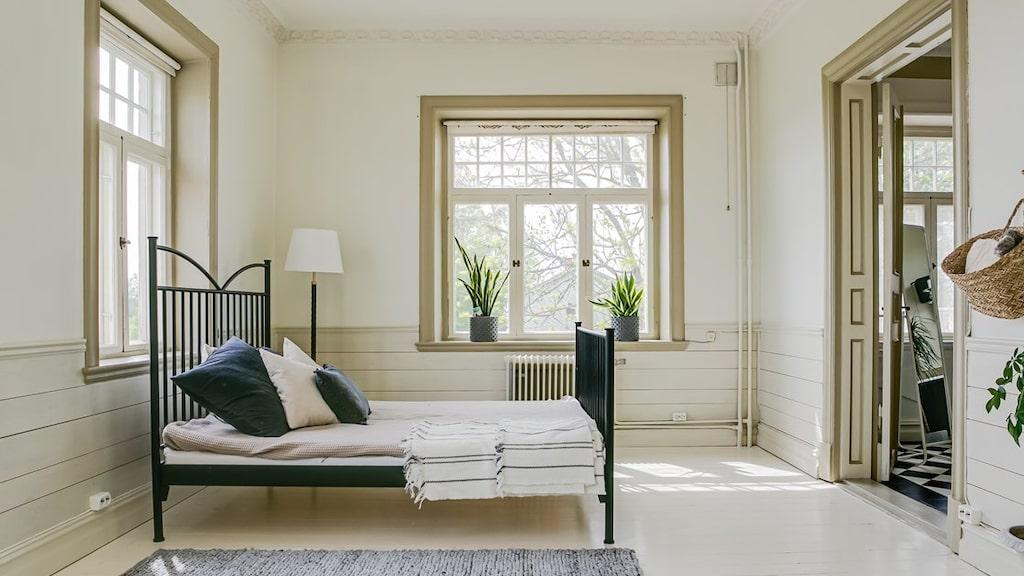 Sovrum med vitmålat trägolv, bröstpanel och målade väggar.