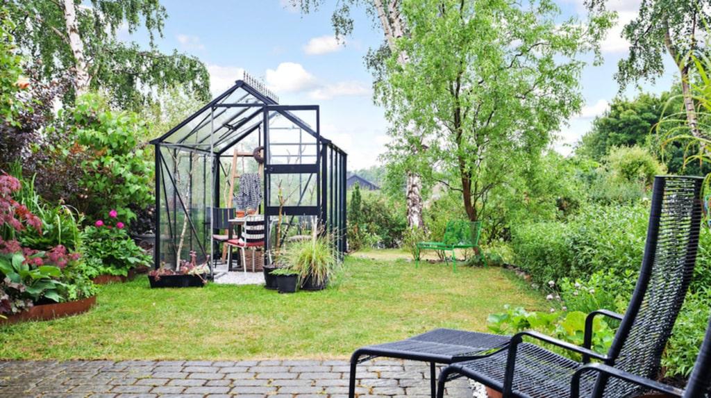 Stensatt uteplats och mysigt växthus för den med gröna fingrar.