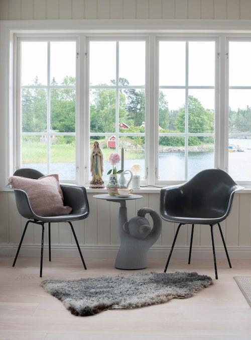 """Glasverandan rymmer också en liten sittgrupp med moderna stolar och ett bord som har blivit en riktig """"conversation piece"""". Bord, Monkey table, design, Jaime Hayon. Stolar, Vitra. Statyn i fönstret är köpt i en antikaffär i Köpenhamn och är en fin kontrast till den moderna sittgruppen."""