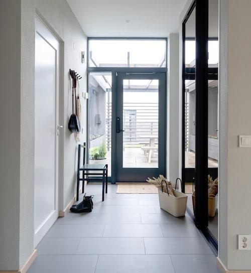Stora fönster och en glasad ytterdörr gör att hallen känns ljus och välkomnande. Inbyggda garderober gömmer alla skor och ytterkläder. Till vänster ligger ett mindre badrum.