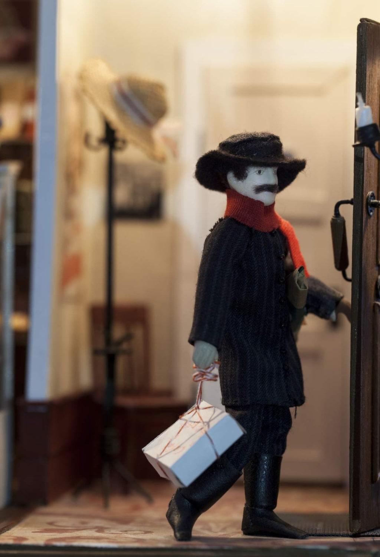 Vladimir är på väg ut genom dörren med sin tårta. I hallen står en tamburmajor av metalltråd.