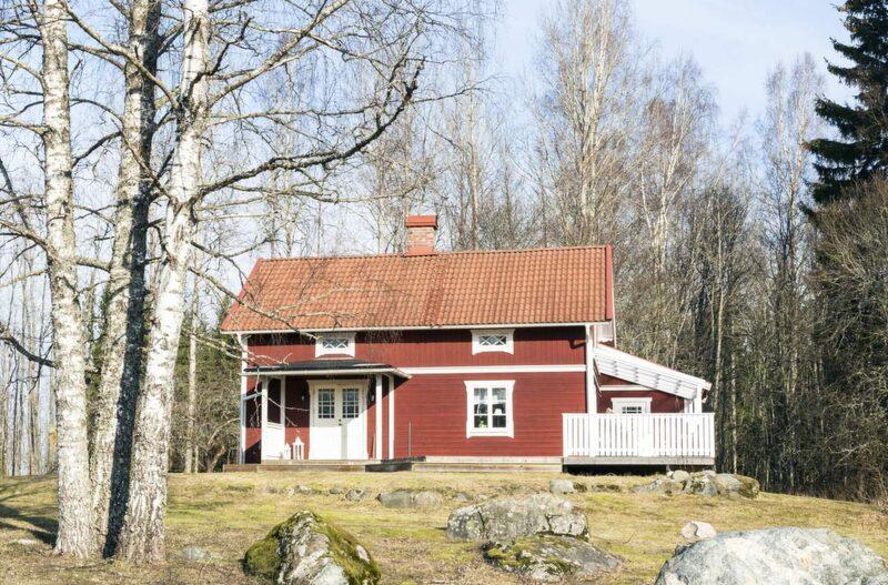 Falurött. Det röda, gamla huset ligger vackert på en liten kulle omgivet av skog och ängar.