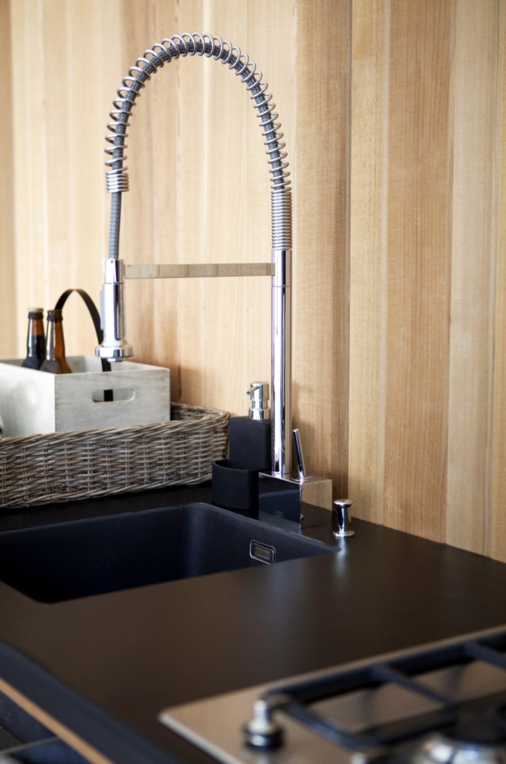 """Köksväggen är byggd av slät cederpanel i olika bredder. Ovandelen av köksbänken är inklädd i mattsvart plastmatta. Ho från """"Franke"""". Blandare från """"Franke""""."""