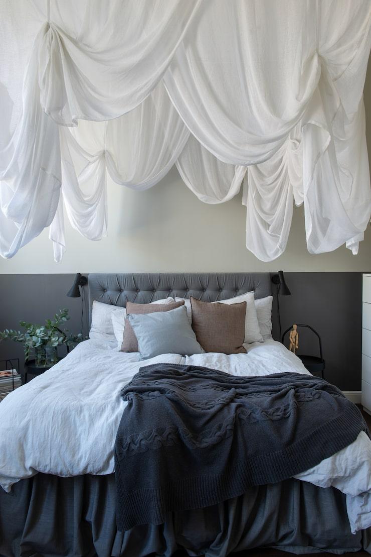 Över parets säng hänger en baldakin köpt på Ellos. Sänggaveln är egengjord av en gammal madrass och en gardin. Sängbord, Ikea. Sänglampor, Louis Poulsen/Arne Jacobsen.