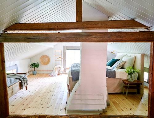 Sovrummet ligger på husets övervåning. Här finns många fint bevarade bjälkar. Nattduksborden är loppisfynd. Sängen kommer från Mio och kuddarna från Åhléns.