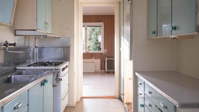 Köket med ljusblå köksluckor, gasspis och plastmatta.