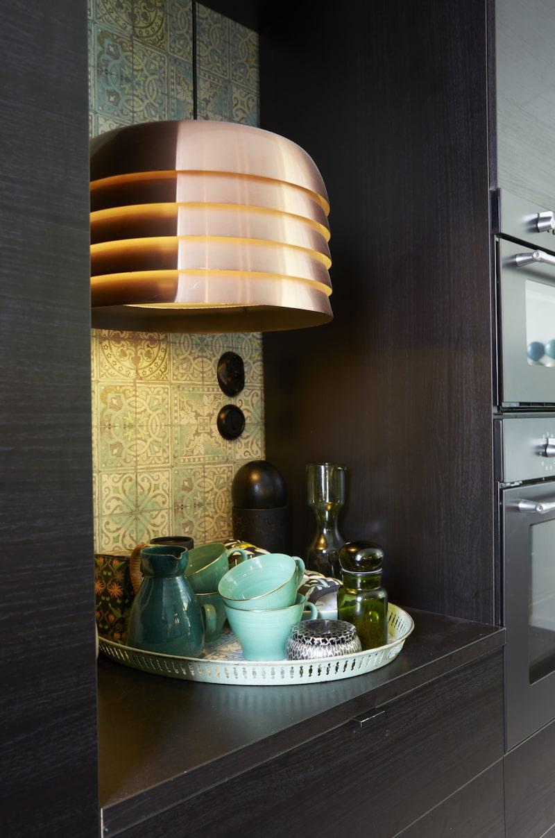 Kontraster. Vintagelampan i koppar, design Hans Agne Jakobsson, är köpt på loppis och utgör en fin kontrast mot det nya köket.
