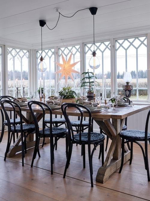 Den vackra glasverandan med sina stora fönster med utsikt över åkrarna är ett nybygge men ser ut som om den alltid funnits där. Lampor över bordet, Watt & Veke. Bord, Artwood. Stolar, Trendrum.