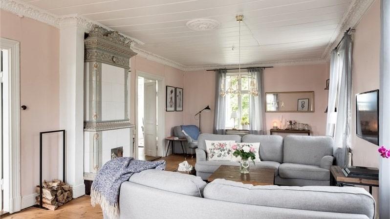 Vardagsrum med kakelugn och vackra stuckaturer i taket.