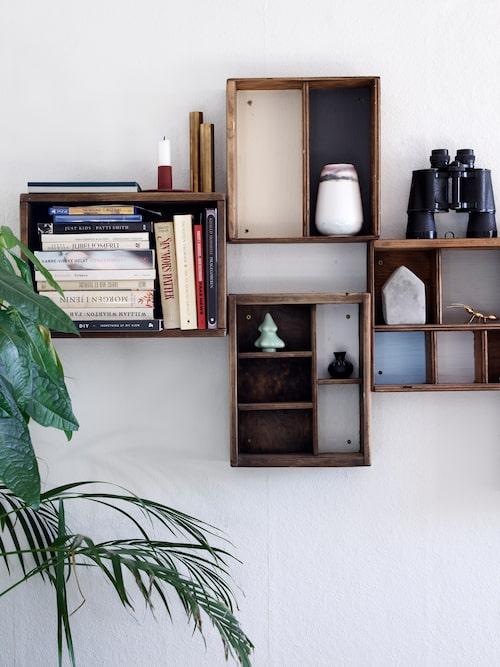 I vardagsrummet har Fie och Jonas har byggt en personlig bokhylla av gamla trälådor. Mässingsljusstakarna kommer från By Holmer. Den röda ljusstaken kommer från Ferm Living och vasen från Margit Brandt. Betonghuset och prydnadsgranen kommer från Søstrene Grene.