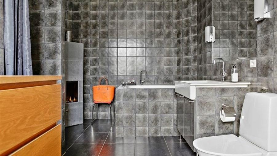 Badrummet i grått kakel har också en vedkamin. Mysigt att ligga och titta på i badet.