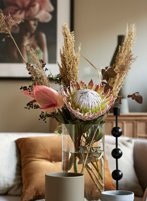 Cylindervas i glas, 998 kr, Kristina Stark. Svart ljusstake Otto, 998 kr, Posh Living. Blommor, Floristkompaniet.