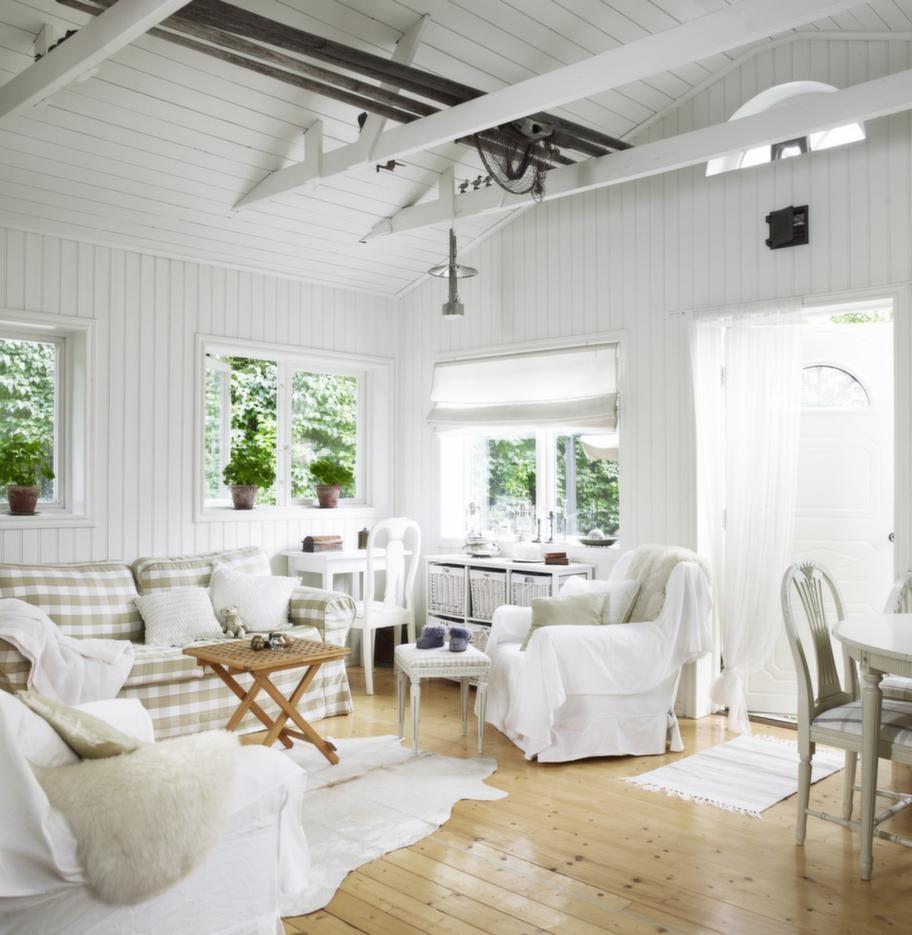 <strong>Harmoniskt.</strong> Det stora allrummet är ett harmoniskt pussel av väl valda detaljer och möbler. Soffa, fåtöljer och vita fårskinn från Ikea. Virkade kuddar från Drömhuset, handsydd hissgardin, vit koskinnsmatta från Rusta, lilla fällbordet, Asko, skänken med korgar, Jysk och årorna i taket från Rosenhills loppis.