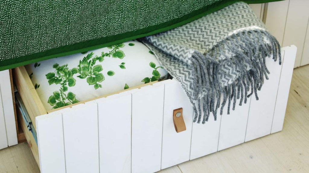 Utrymmet under sängen rymmer rejäla lådor klädda med vitmålad träspont för ett enhetligt intryck. Kudde, 199 kronor, Indiska. Pläd från Klippan, 625 kronor, Habitat.