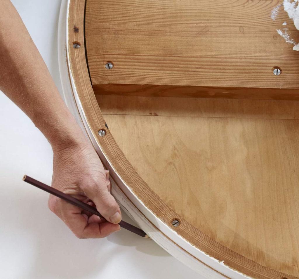 RITA UPP. Lägg bordet upp och ner för att rita av formen på baksidan av tapeten.