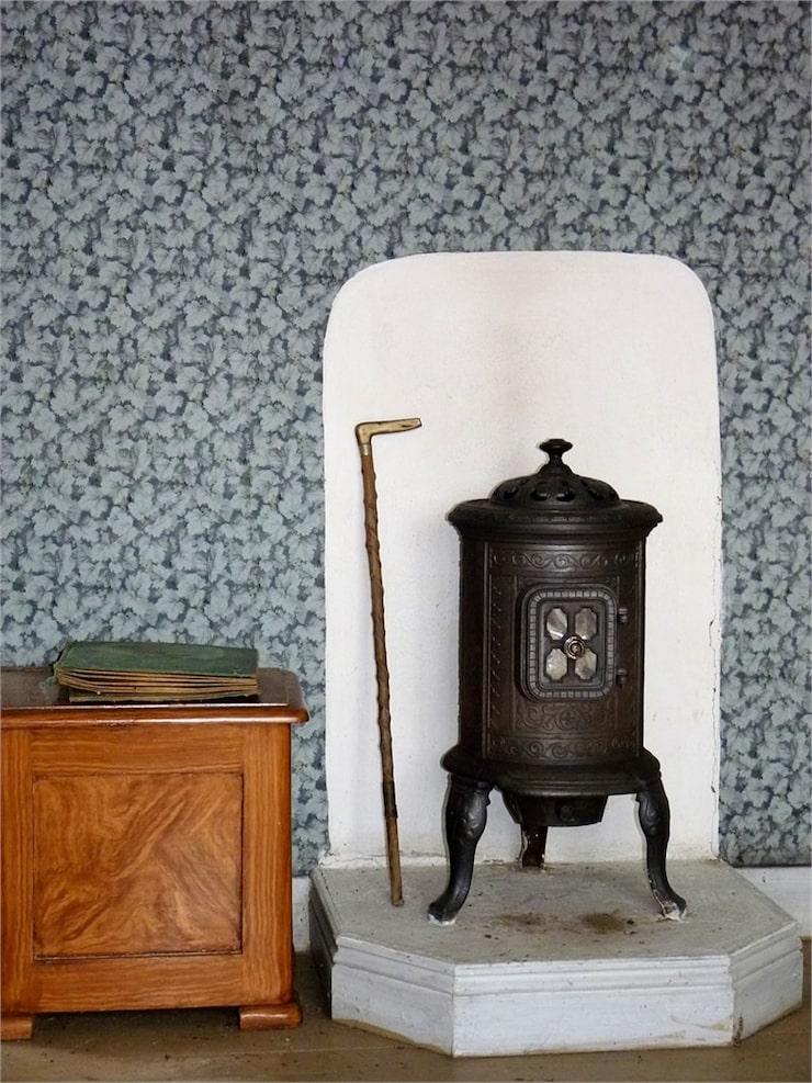 På övervåningen har två av sovrummen charmiga gjutjärnskaminer.