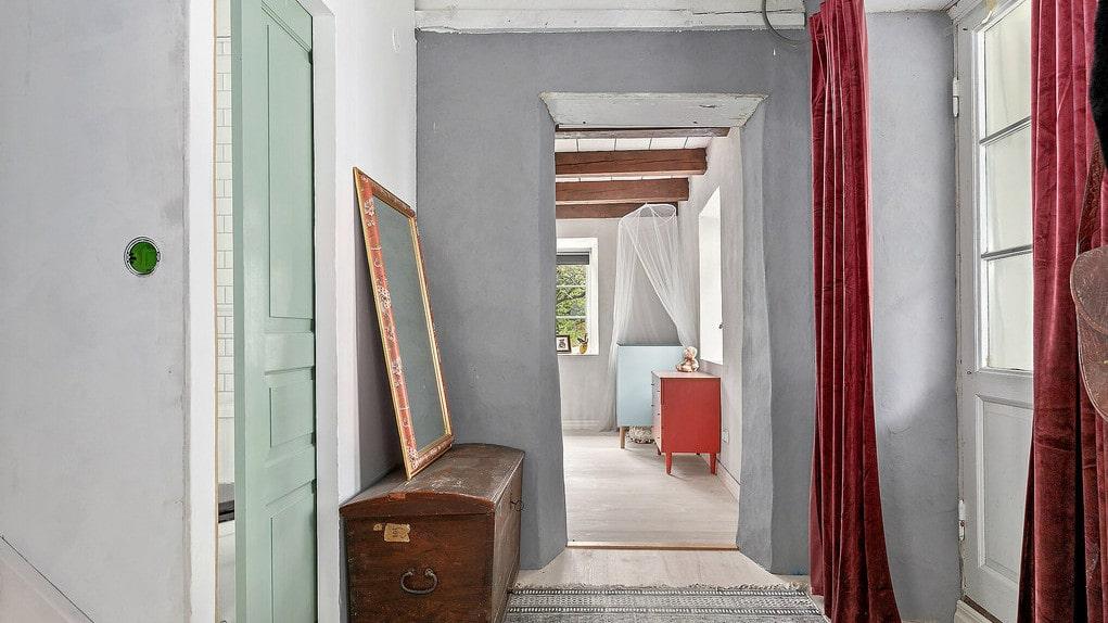 I hallen finns dels en utgång till veranda på husets framsida, via vackra pardörrar, och dels en trappa som leder upp till den nybyggda övervåningen. Även badrummet nås från hallen.