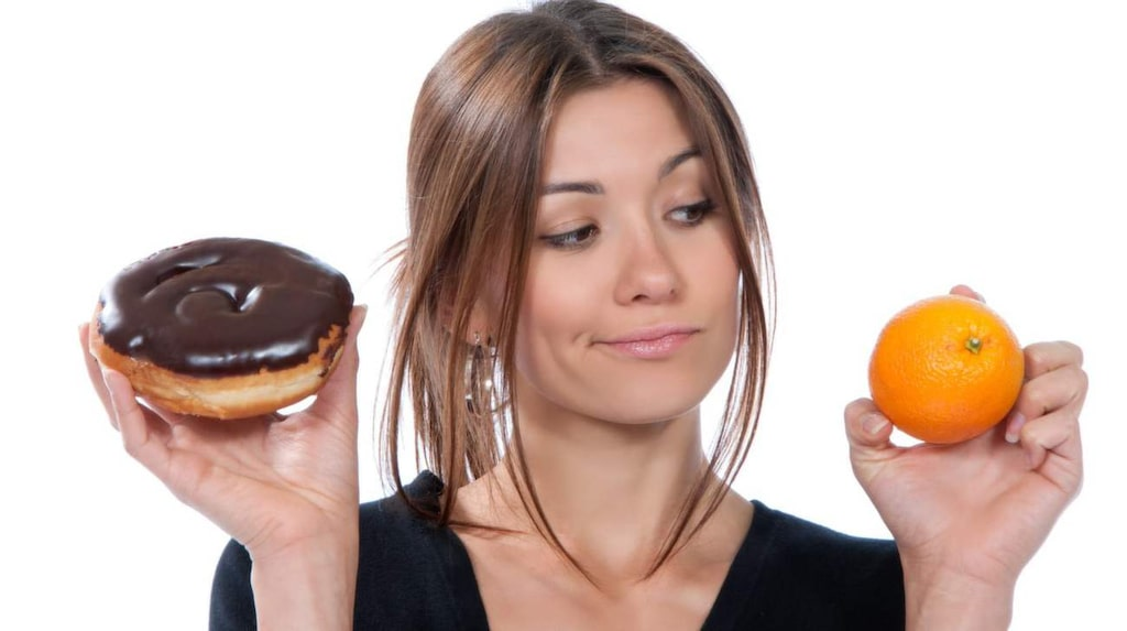 healthy eating food concept. woman comparing unhealthy donut and orange fruit thinking isolated on a white background, apelsin, godsak, mellanmål   publicerad text: